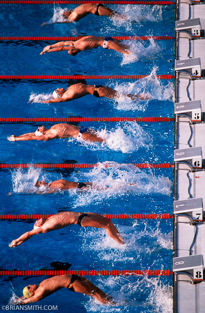 Swimmers leave the blocks at the start of a backstroke race at the 1984 Los Angeles Olympics