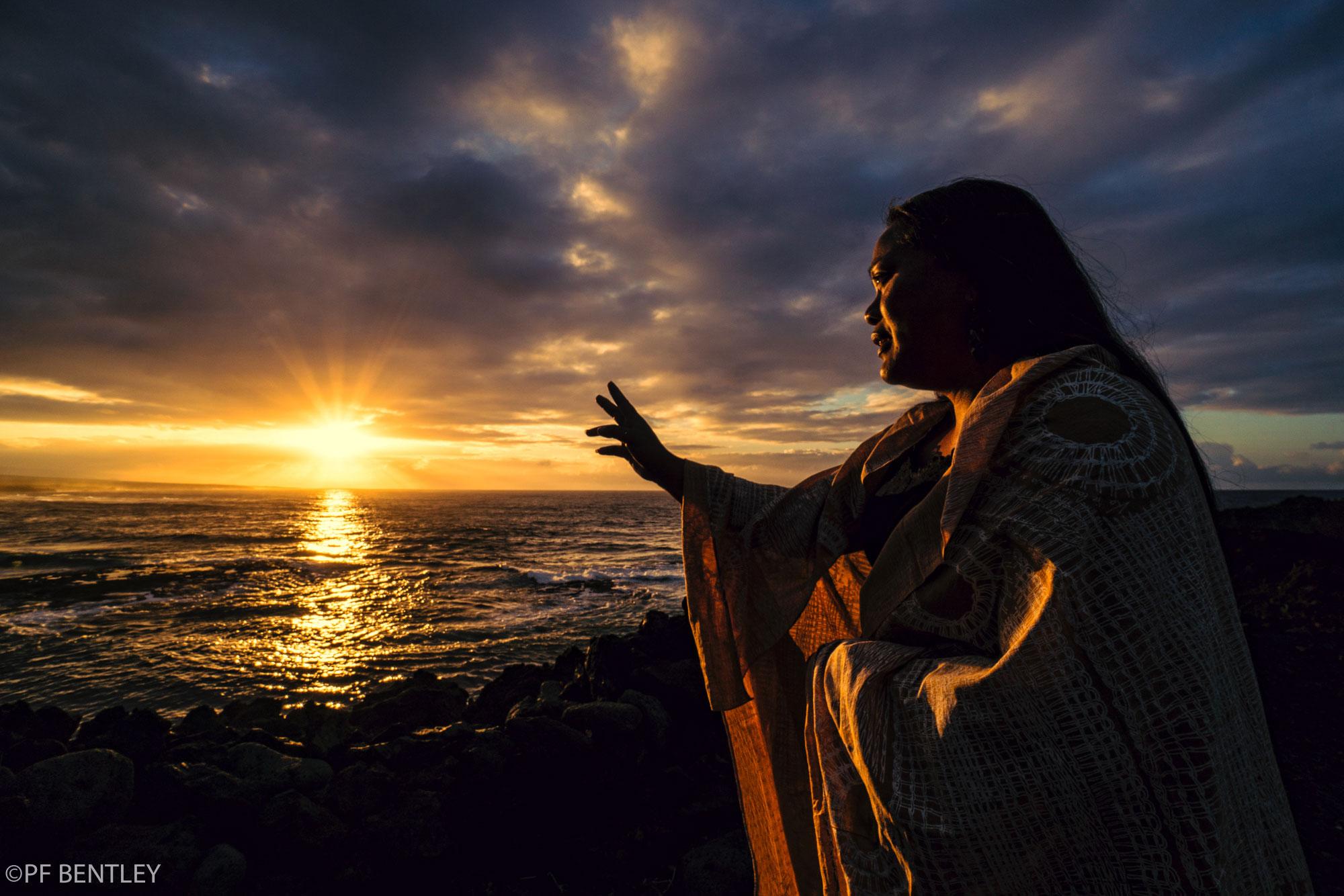 Ka'u native Nohea Ka'awa greets dawn atop the Ka'ie'ie Heiau overlooking Ninole beach.